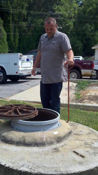 City Employee Inspecting Manhole